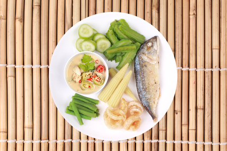 Isolated of Ready Thai food served, Green chili dip as Nam Prik Num in Thai with deep firedmackerel,crispy pork rind ,boiled cow-pea,wing bean ,corn and sliced cucumber. Have text space on right.