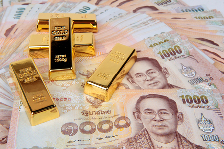 5 of 1 kg. Gold bar on the 1000 Baht of Thailand banknotes nested a pile high. Stock Photo