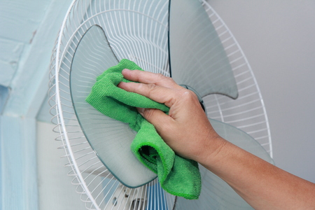 Use a green cloth to wipe the hand grab the blades of the wall tide of electric fan for cleaning. Stok Fotoğraf - 107486996