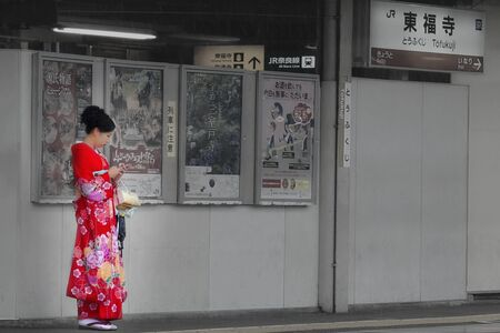 Women wearing red kimono patterned flowers stand hold smartphone under fluorescent light when it rains during journey Tofukuji railway station. Photo has soft and burry.