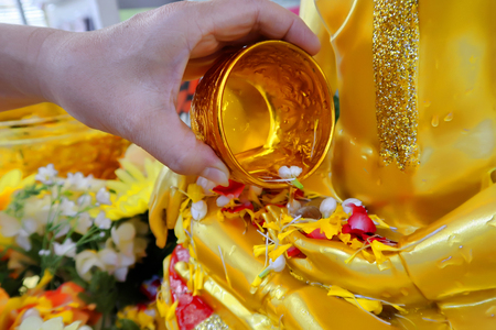 Pour some water with refreshing and colorful flower in metallic gold bowl on the hand of golden Buddha image to worship in the Songkran Festival.