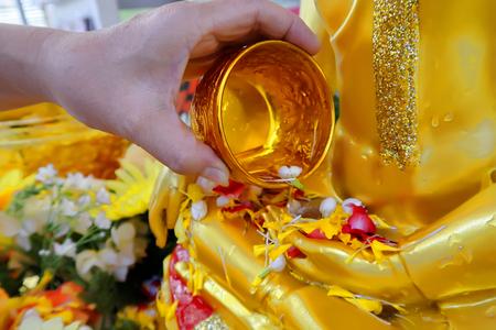 Versa dell'acqua con un fiore rinfrescante e colorato in una ciotola d'oro metallico sulla mano dell'immagine dorata del Buddha per adorare al Songkran Festival. Archivio Fotografico