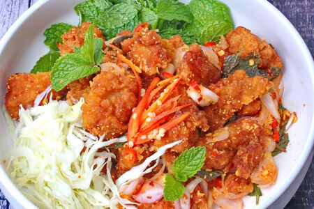 Thai food, Spicy crispy deep-fried chicken salad call Yum Kai Zap in Thai topped shredded cabbage and Kaffir lime leaves.