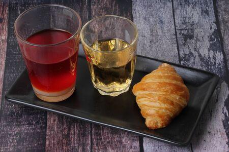 Thai Traditional milk tea served with tea and croissant served on old wood. 版權商用圖片
