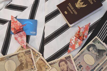Passport,money banknotes, credit card and origami paper birds place on japanese pajamas call as yukata