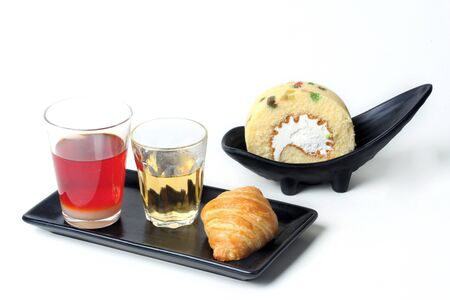 Thai Traditional milk tea served with tea, croissant and roll fruit cake served on white background.