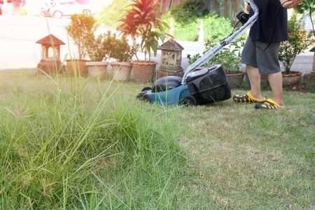 Use hands to push mower to cut the grass in garden of  house