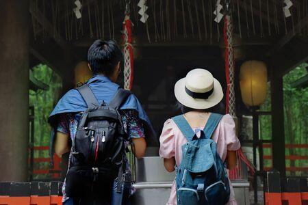 Backpack teen boy and girl respect belief by beautiful mind together within shrine at Arashiyama bamboo grove. 版權商用圖片
