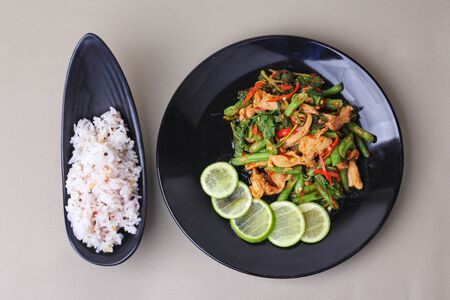 Thai cuisine , Spicy fried cowpea and basil with pork topped sliced green lemon served with japanese seed for rice in jasmine rice on black plates