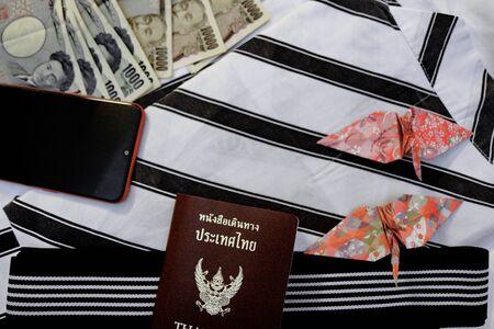 Passport,mobile phone,money banknotes, credit card and origami paper birds place on japanese pajamas call as yukata 版權商用圖片