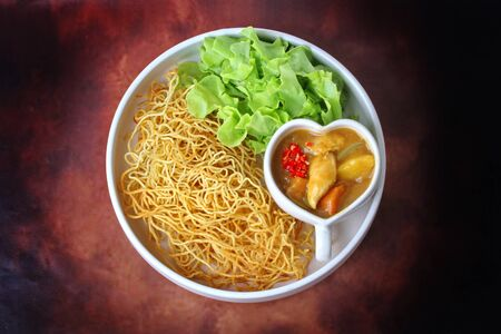 Ready served of  crisy  noodle with Japanese yellow curry topped green oak.