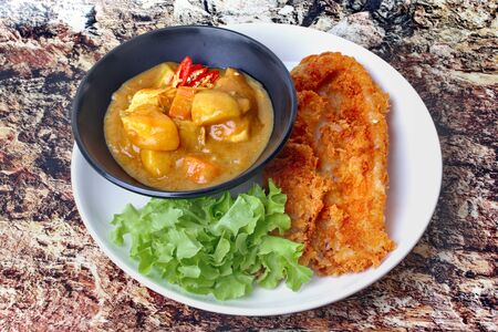 Ready served of crispy fried dolly fish with Japanese yellow curry topped green oak.