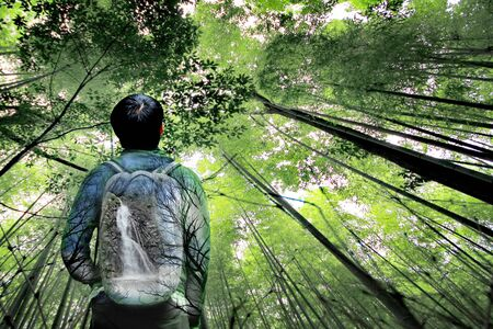 Overlay waterfall and forest on bag of  backpack behind tourist teen boy with bamboo forest at Arashiyama,Kyoto,Japan. Isolated of man. Archivio Fotografico