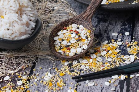 16 Traditional  seed  cereals for cooking with rice from Japan and ready served of Thai jasmine rice that has been cooked with Japanese cereals on old wooden pattern.