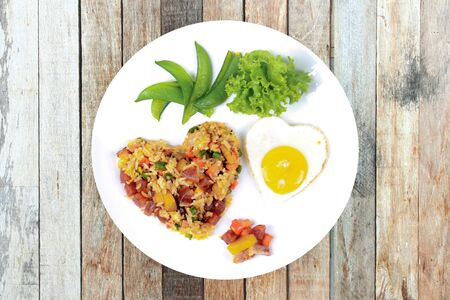 Isolated of  Colorful Chinese sausage fried rice and sunny egg in heart shapes with mixed vegetable as peas, pumpkin, taro, tomatoes, carrots and sweet peppers. 版權商用圖片