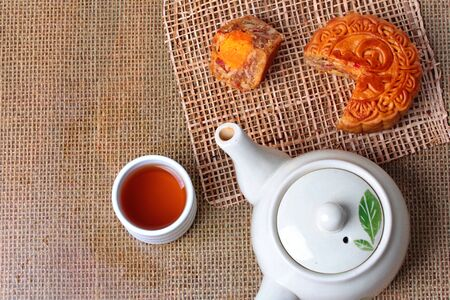 Round mooncake filled  8 grains and salted eggs served with tea and teapot.