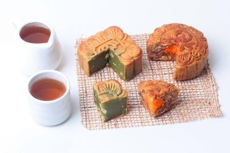 Round mooncake 8 grains and salted eggs and squred shaped moon cakes, red beans, stirred in green tea and chopped macadamia nuts served with tea and teapot.