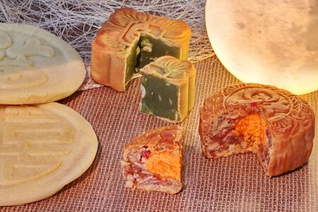 Round mooncake filled 8 grains and salted egg  and square mooncake filled red bean paste stirred in green tea and chopped macadamia nuts served with  two green bean mooncakes placed on sackcloth near moon shaped light. 版權商用圖片