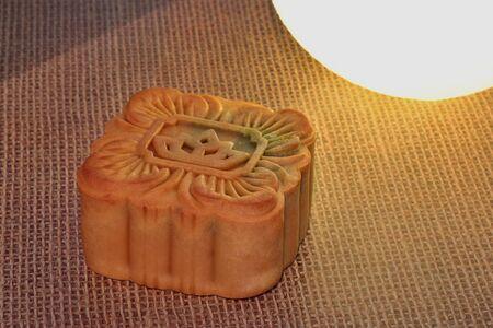Square shape mooncake Placed on sackcloth near the moon shaped light Banco de Imagens