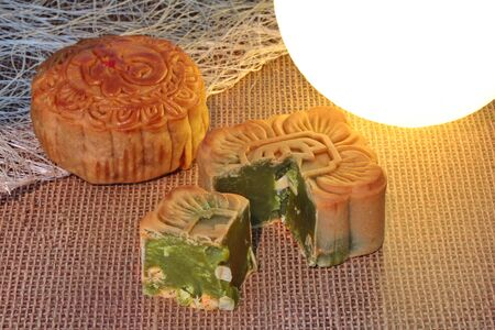 Square shape mooncake filled red bean paste, stirred in green tea and chopped macadamia nuts  in front of the round round moon cake is placed on a sackcloth near the moon-shaped light. Banco de Imagens