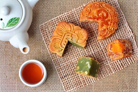 Round mooncake 8 grains and salted eggs and squred mooncake filled red beans, stirred in green tea and chopped macadamia nuts served with tea and teapot.