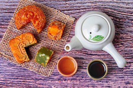 Round mooncake  8 grains and salted eggs and squred mooncake filled red beans, stirred in green tea and chopped macadamia nuts served with tea and teapot. 版權商用圖片