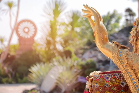 Palm of left hand and the right hand hold  colorful bowl of the outdoor Buddha statue.  And free space for text.