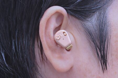 Small hearing aid put in the right ear. Stok Fotoğraf