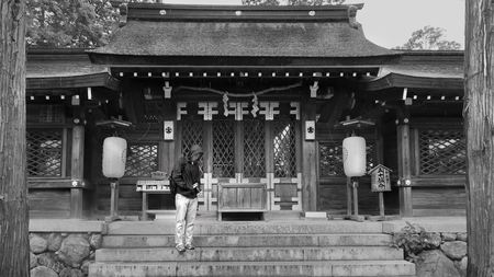 Wakayama City,Japan,14 July 2019,Black and white photo of Tourist Backpacker teen is standing and protecting  body and  DSLR camera in font of Buddhist building of  Itakiso Jinja Shrine. 新聞圖片