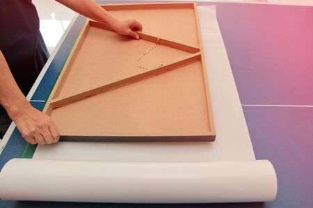 Photo frame technician is placing the floating frame over the double sided adhesive. To stick together
