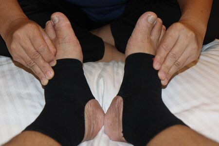 Thailand massage with the use of two hands to massage the ankle.