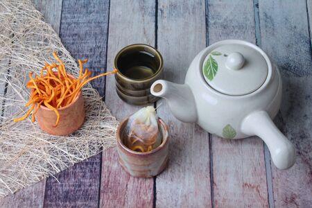 Golden cordyceps mushroom in cup ,herbal tea bag of  golden cordyceps militaris and tea in cup served on wood