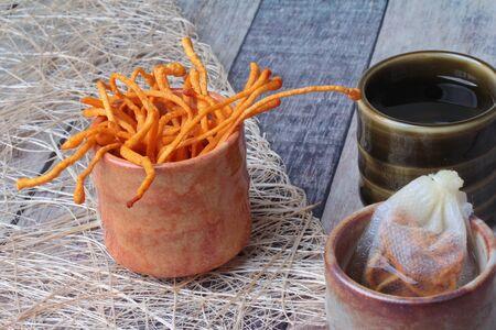 Golden cordyceps mushroom in cup   served on wood Stock fotó