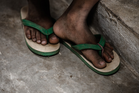 uneducated: close-up the lack of a disadvantaged childs shoes