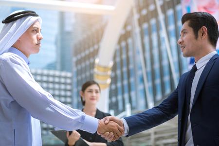 business deal between asian and Arabs peoples working outdoor