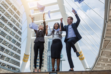 Three business officer happy after project success and throw out the document Stock Photo