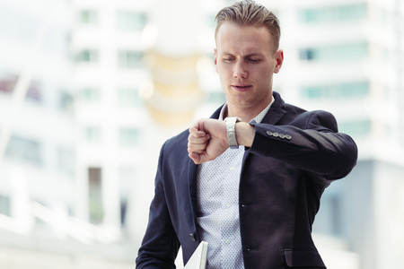 Smart businessguy looking watch in rush hour time