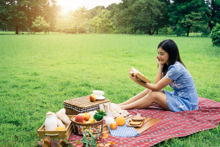 A girl going picnic in a park and reading a book
