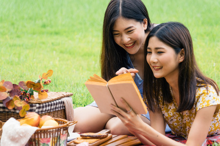 Couple of girls going picnic in a park, reading a book together and feeling friendly.