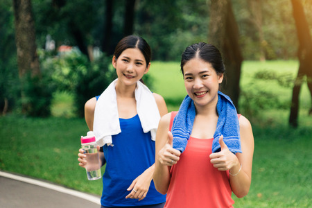 Portrait of girls couple go exercise in a park and feeling friendly