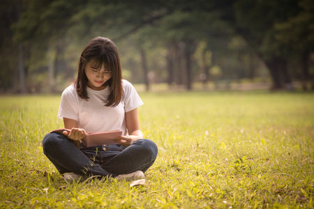 Portrait of high school girls sit down and read a book in park, education concept