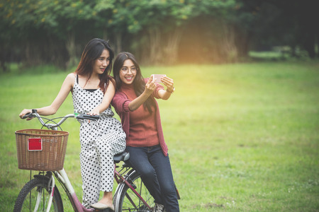 Girls ride a bicycle  in park, having fun by play together Reklamní fotografie