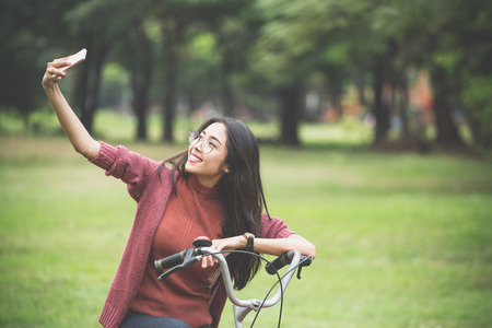 Girl selfie herself and ride on the bicycle in park Reklamní fotografie