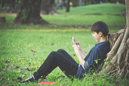 Guy play a smart phone under the tree in park