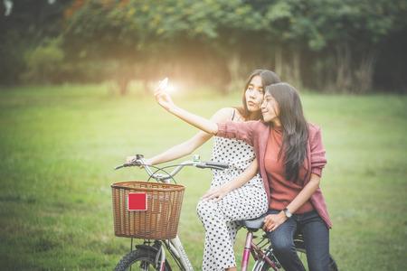 Las niñas andan en bicicleta en el parque, divirtiéndose jugando juntas.