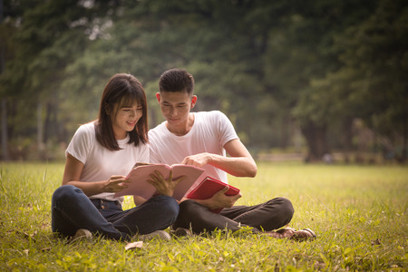 couple of high school students sit down and read a book in park, education concept