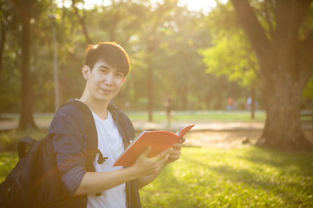 Portrait of high school boy with books and bag in park, education concept Reklamní fotografie