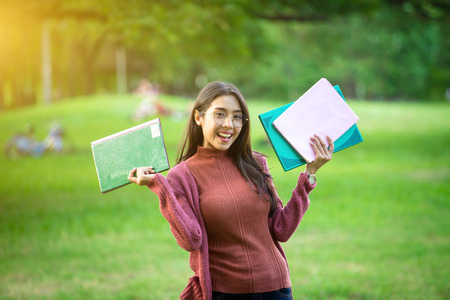 Portrait of high school girl with books in park, education concept