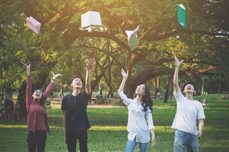 Group of highschool peoples throw the book after finish exam or report in park