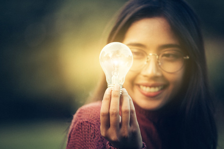 Portrait of young Asian girl with glasses hold a books get bright idea using lamp bulb as icon, in park